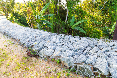 stabilize: Slope and earth retention wall management with rocks and wire mesh cage system in tropical hilly terrain