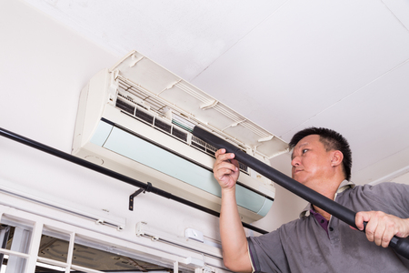 Series of technician servicing the indoor air-conditioning unit. Vacuuming dust and deposits Stockfoto