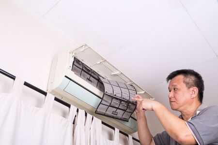 servicing: Series of technician servicing the indoor air-conditioning unit. Inspecting dust filter.