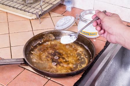 Zuiveringszout om te genieten en te verwijderen ingebrande voedsel in de bodem van de potten en pannen Stockfoto - 54523775