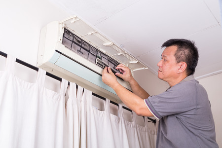 servicing: Series of technician servicing the indoor air-conditioning unit. Removing dust filter.