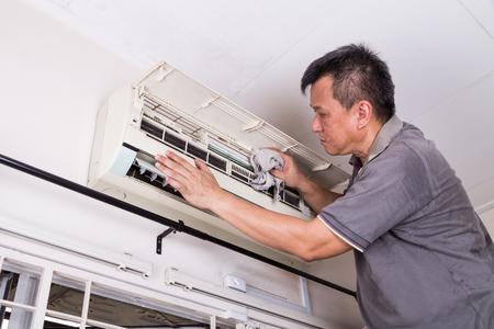 Serie van technicus onderhoud van de indoor air-conditioning unit. Het schoonmaken met een doek.