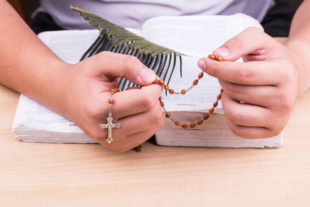 recite: Closeup of hands reciting prayers using Catholic rosary with crucifix and bible