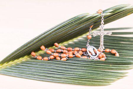 christianity palm sunday: Closeup of Holy Catholic rosary with crucifix and beads on palm leaf