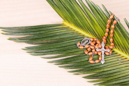 a beads: Closeup of Holy Catholic rosary with crucifix and beads on palm leaf