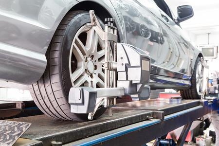 Gros plan du pneu serré avec aligneur subissant l'alignement des roues de l'automobile dans le garage Banque d'images - 54524794