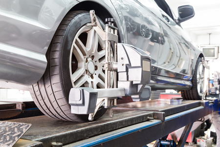 Closeup of tire clamped with aligner undergoing auto wheel alignment in garage