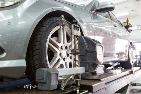 Gros plan du pneu serré avec aligneur subissant l'alignement des roues de l'automobile dans le garage Banque d'images - 54524797