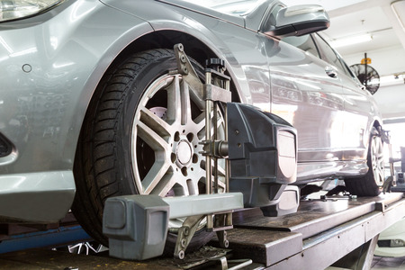 llantas: Primer plano de los neumáticos sujeta con alineador de someterse a la alineación de ruedas de automóviles en el garaje Foto de archivo