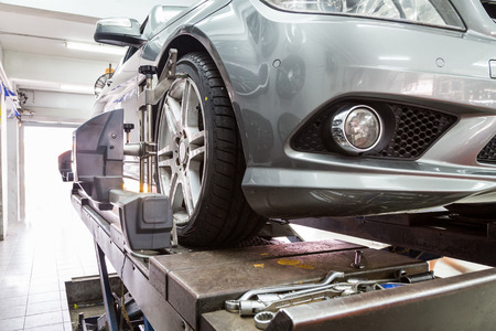 Primer plano de los neumáticos sujeta con alineador de someterse a la alineación de ruedas de automóviles en el garaje