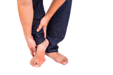 Man in jeans embraces foot with painful and swollen gout inflammation 스톡 콘텐츠