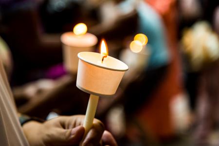luz de velas: Primer de los hombres que llevan a cabo la vigilia de velas en la oscuridad que expresan y que buscan esperanza Foto de archivo