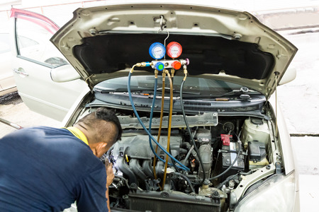 Manometer being used to gauge air conditioning pressure in auto vehicle at garage