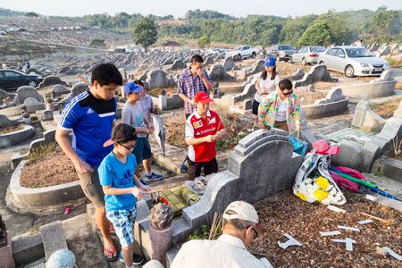 KUALA LUMPUR, MALAYSIA, April 2, 2016: Chinese descendants cleaning tomb and offering prayers to ancestors during the annual QingMing, or tomb sweeping day at cemetery in Malaysia
