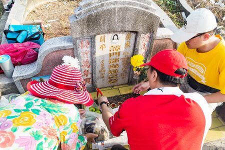 ancestors: KUALA LUMPUR, MALAYSIA, April 2, 2016: Chinese descendants cleaning tomb and offering prayers to ancestors during the annual QingMing, or tomb sweeping day at cemetery in Malaysia