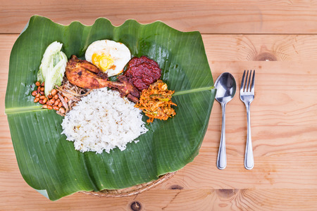 nasi: Traditional nasi lemak meal on banana leaf with fried chicken, anchovies, groundnuts, fried eggs, acar and cucumber. Popular cuisine in Malaysia, Indonesia and Singapore