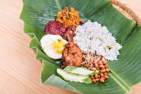 leaf vegetable: Traditional nasi lemak meal on banana leaf with fried chicken, anchovies, groundnuts, fried eggs, acar and cucumber. Popular cuisine in Malaysia, Indonesia and Singapore