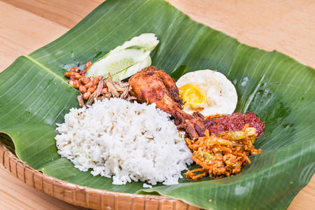 lemak: Traditional nasi lemak meal on banana leaf with fried chicken, anchovies, groundnuts, fried eggs, acar and cucumber. Popular cuisine in Malaysia, Indonesia and Singapore