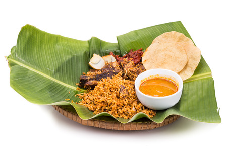 indian culture: Aromatic delicious nasi briyani meal with mutton and dhal on banana leaf and rattan plate, a popular Indian cuisine