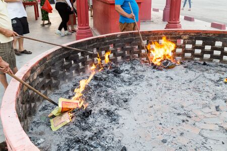 burning money: Chinese devotees burning paper offerings during QingMing celebration at temple