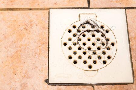 Mechón de pelo atrapado en el cuarto de baño ducha salida de la trampa de drenaje Foto de archivo - 56211623