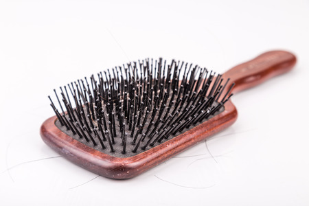 strand of hair: Comb with strand of hair sticking on it against white background Stock Photo