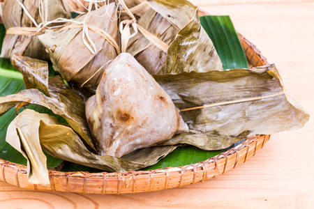 unwrapped: Freshly steamed Chinese rice dumpling on traditional rattan tray, with one already unwrapped