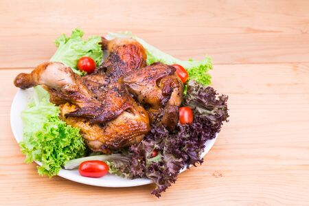 whole chicken: Juicy grilled roast whole chicken with herb, salad and tomato garnish on wooden table Stock Photo