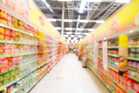 Sfocato, lungo corridoio illuminato alimentari colorato in un moderno negozio di ipermercato