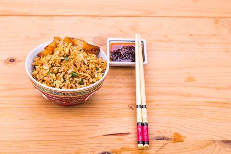 arroz chino: arroz frito picante china delicioso con cerdo asado servido en un tazón en mesa de madera Foto de archivo