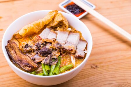 roast pork: Delicious spicy curry noodle with roast pork, cockles, vegetable. Popular delicacy in Malaysia and Singapore Stock Photo
