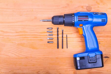 cordless: Flatbed of convenient cordless drill cum screwdriver set with bits on wooden background