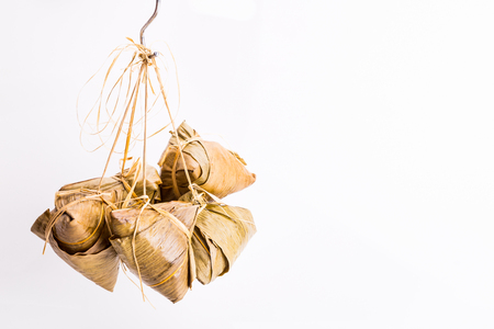 Bunch of Chinese rice dumpling or zongzi tied hanging against white background Banco de Imagens