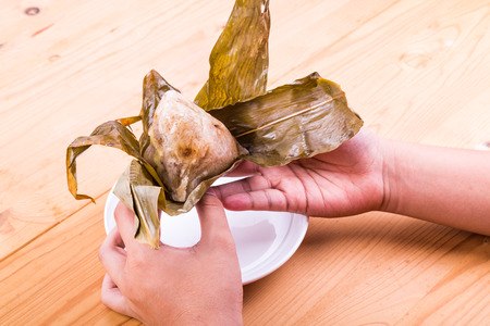 unwrapping: Hand unwrapping freshly cooked Chinese rice dumpling or zongzi on table