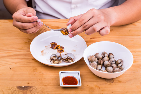 cockles: Person extracting cockles from its shell for consumption with chili dips.  Delicacy among Asians. Stock Photo