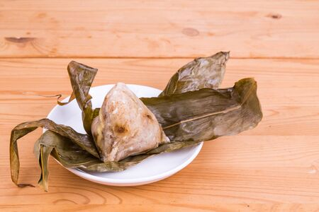 unwrapped: Freshly prepared delicious Chinese rice dumpling or zongzi unwrapped on plate