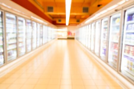 brightly lit: Defocused brightly lit frozen food aisle with refrigerator in modern supermarket Stock Photo