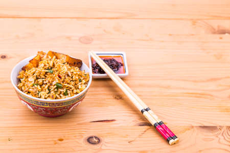 roast pork: Delicious Chinese spicy fried rice with roast pork in bowl served on wooden table Stock Photo