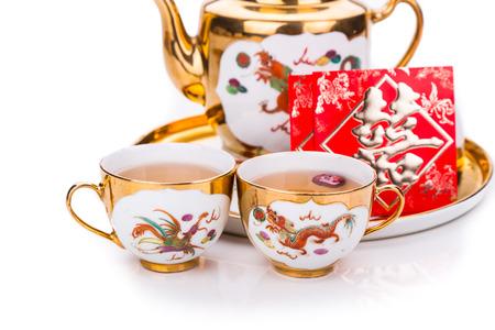 結婚式: 汎用赤封筒ホワイト バック グラウンドで word のダブルハピネスを軸受と一般的な伝統的な中国茶セットのクローズ アップ 写真素材