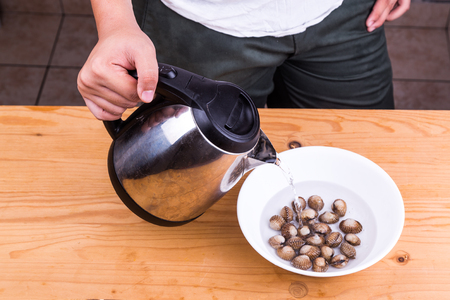 cockles: Person pouring boiling water over cockles in bowl as part of cooking preparation