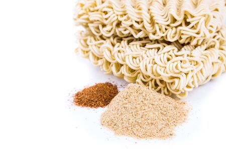glutamate: Unhealthy flavoring powder with uncooked instant noodles in background isolated in white