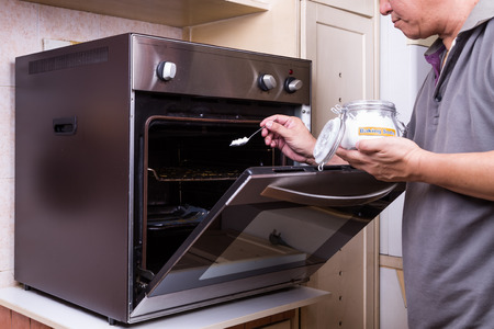 bicarbonate: Person sprinkling baking soda into an oily oven as cleansing agent to clean