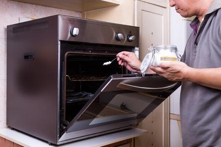 Persoon strooien baking soda in een olieachtige oven als reinigingsmiddel schoon te maken Stockfoto