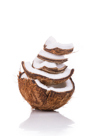 Old brown organic coconut fruit copra broken into pieces and stacked on white background and vertical format