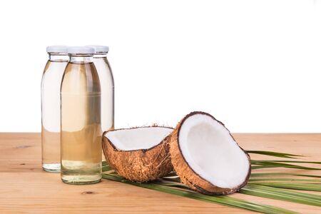 Prensado en frío de aceite de coco virgen extra en botellas de coco con frutas como fondo