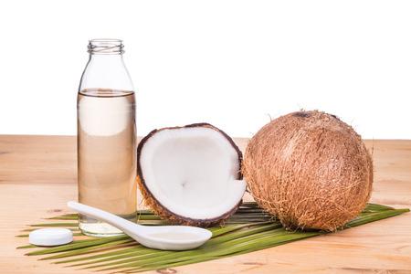 aceite de coco: Prensado en frío de aceite de coco virgen extra en botellas de coco con frutas como fondo Foto de archivo