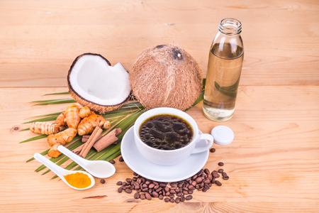 aceite de coco: A prueba de balas café mezclado con prensado en frío de aceite extra virgen de coco, la cúrcuma y el clavo en la mesa de madera, dieta cetogénica sana