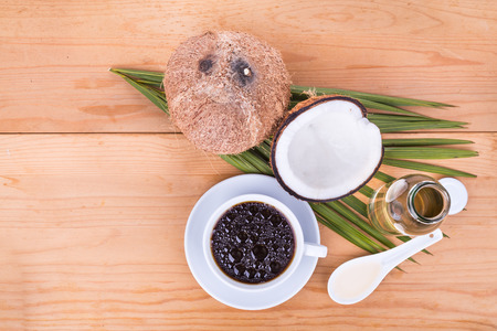 aceite de coco: Vista de arriba del café de balas con prensado en frío de aceite de coco virgen extra en la mesa de madera, parte de la dieta cetogénica