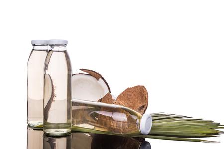 coco: Prensado en frío de aceite de coco virgen extra en botellas de coco con frutas como fondo Foto de archivo
