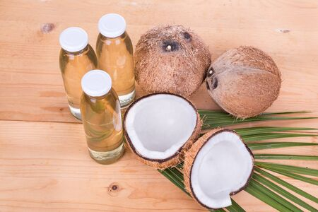 extra virgin: Top view of cold pressed extra virgin coconut oil in bottles with coconut fruits as background